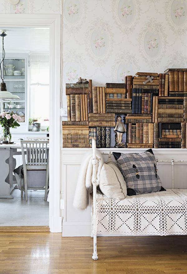 Vintage couch with white metal frame and lacy throw in front of stacked, antiquarian books on sideboard; view into dining room t