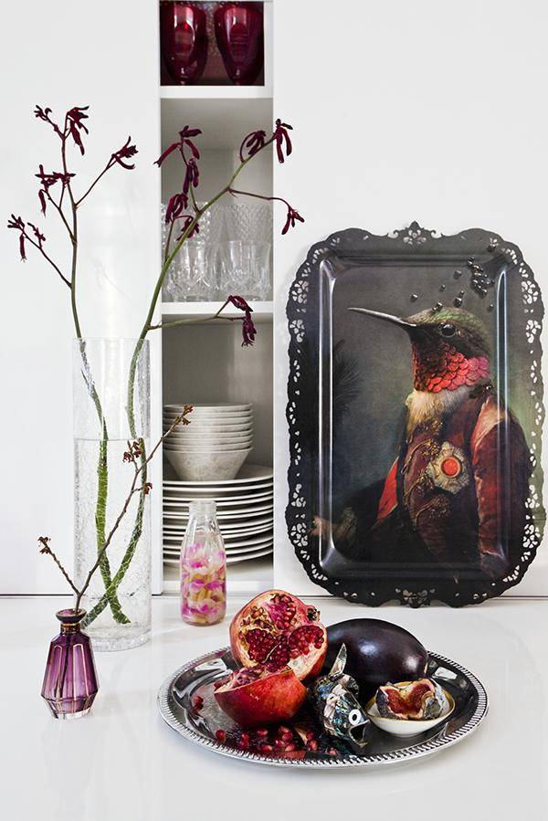 Decorative tray with bird motif, spindly twigs in vases and pomegranate in front of kitchen shelving