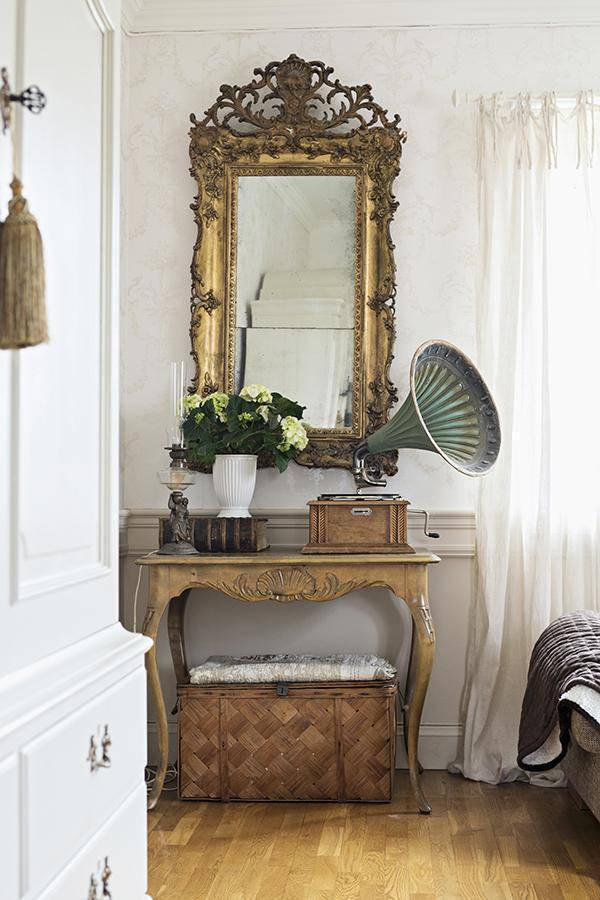 Vintage gramophone on console table with curved legs below antique, gilt-framed mirror on wall