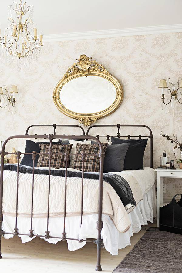 Vintage, twin beds with wrought iron frames below antique, oval, gilt-framed mirror on wallpapered wall