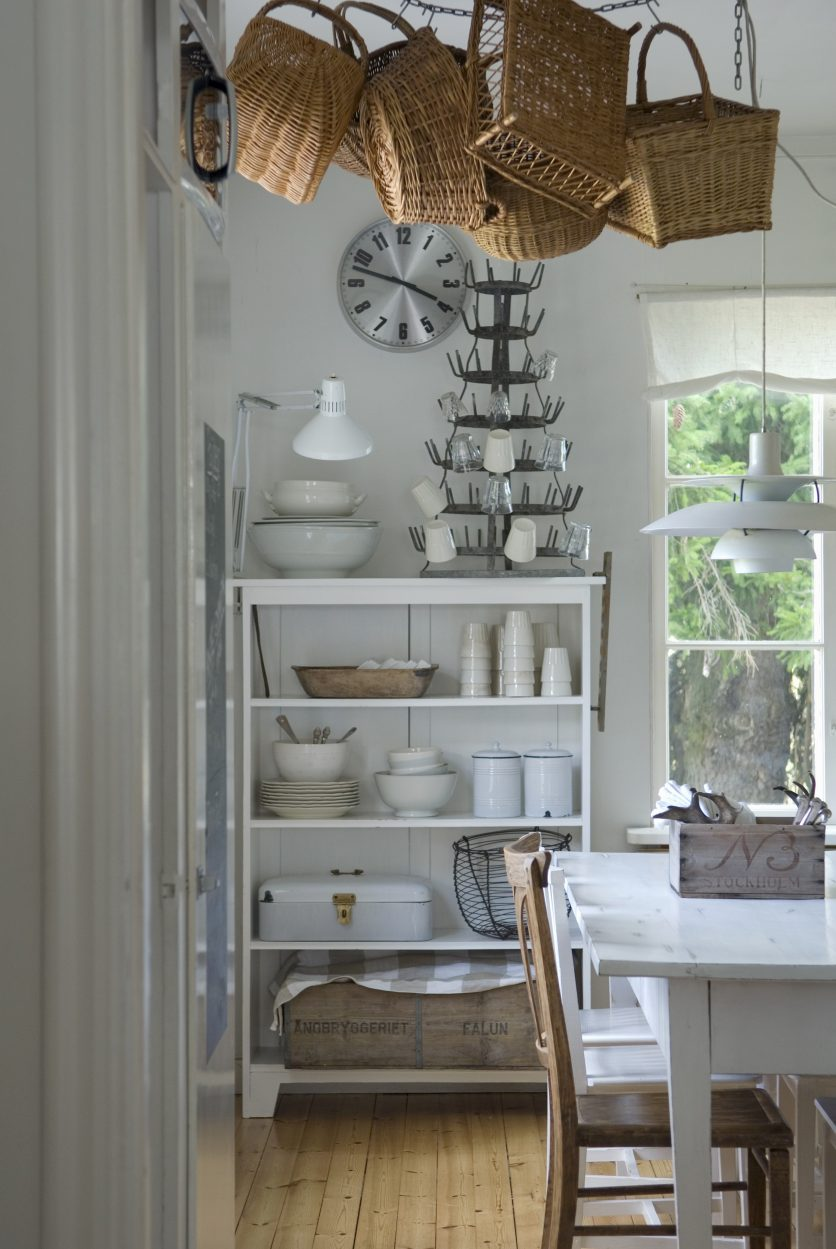 Corner of dining room with white dining set, baskets hanging from ceiling and white-painted, open-fronted shelves of crockery ag